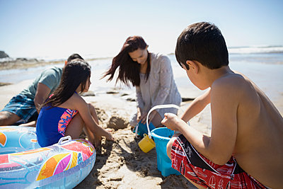 Latino family making sandcastle on sunny beach - p1192m1418562 by Hero Images