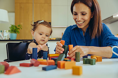 Happy mother and baby daughter playing with building blocks - p300m2042745 by Mareen Fischinger