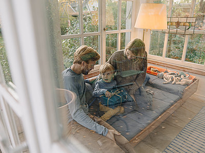 Little boy with parents unwrapping gift in sunroom at home - p300m2205513 by Kniel Synnatzschke