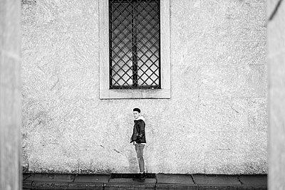 Portrait of distant man standing underneath window on sidewalk - p555m1481984 by Fabio Camandona