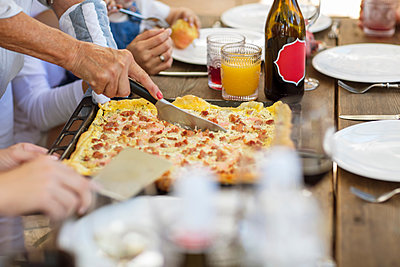 Woman cutting up pizza at lunch table - p924m1493732 by Zero Creatives