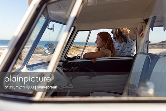 Happy young couple looking away near camper van at beach - p1315m2117893 by Wavebreak