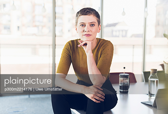 Portrait of businesswoman sitting on desk in office - p300m2214176 by Uwe Umstätter