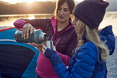 Two women with hot drink camping at lakeshore - p300m1563059 by Philipp Nemenz