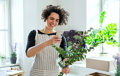 Smiling young woman taking smartphone picture of flowers in a small shop - p300m2143819 by HalfPoint