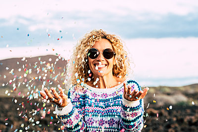 Portrait of happy blond woman celebrating with confetti, Tenerife, Spain - p300m2155761 by Simona Pilolla