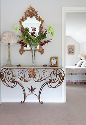 Cut flowers on metalworked console with gilt mirror in Sussex home  UK - p3493572 by Robert Sanderson