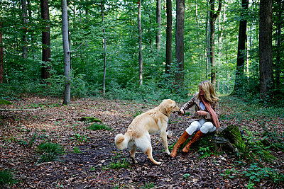 A woman is playing fetch with a dog in the forest - p728m729070 by Peter Nitsch