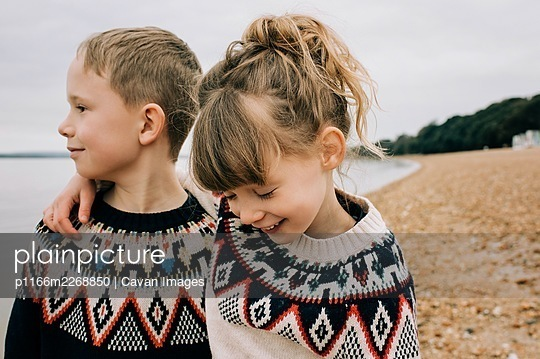 siblings hugging and laughing together on the beach in the UK - p1166m2268850 by Cavan Images
