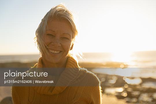Woman enjoying time by the sea - p1315m2162406 by Wavebreak