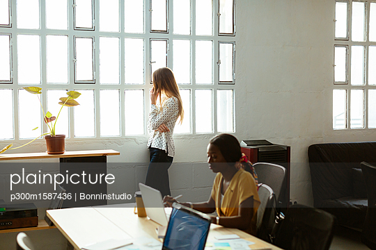 Two women using cell phone and laptop in office - p300m1587436 von Bonninstudio