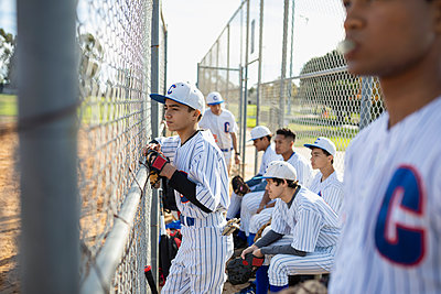 Baseball player watching game behind fence - p1192m2062501 by Hero Images