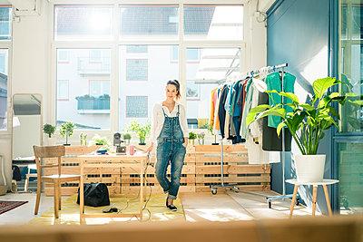 Fashion designer standing in her studio - p300m1580693 von Robijn Page