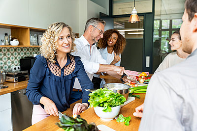 Businesswoman cutting vegetable while talking to colleagues in office kitchen - p300m2241105 by Peter Scholl