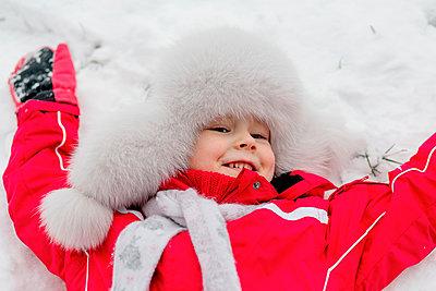 Smiling girl lying in the snow - p300m2277009 by Oxana Guryanova