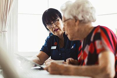 Caretaker assisting senior woman in using digital tablet at home - p426m1468268 by Maskot