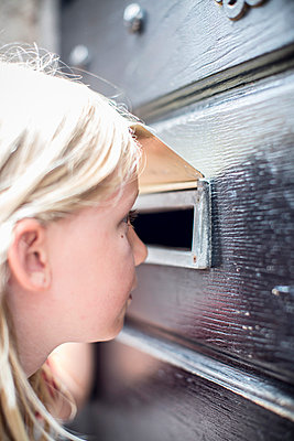 Side view of girl looking through mail slot in door - p426m858099f by Maskot