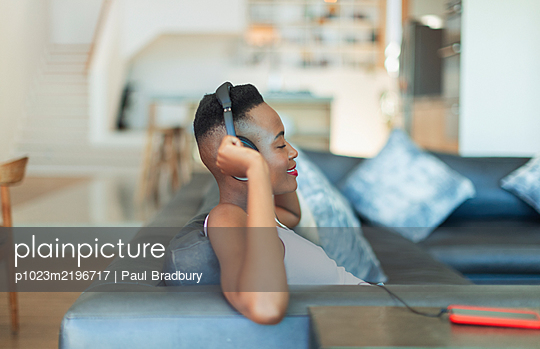 Smiling, serene young woman listening to music with headphones and mp3 player on living room sofa - p1023m2196717 by Paul Bradbury