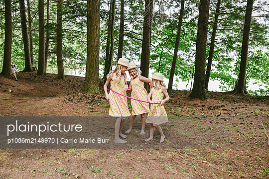 Three girls playing with Hula hoop - p1086m2149970 by Carrie Marie Burr