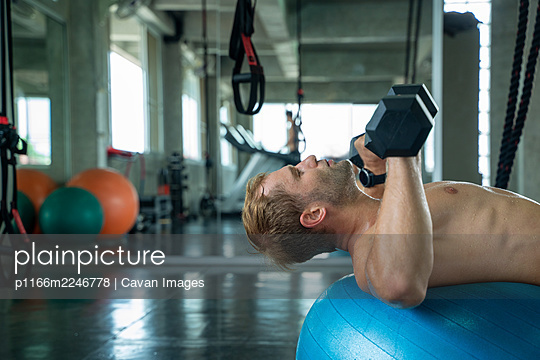 Strong man exercising with dumbbells in a gym,Athlete builder mu - p1166m2246778 by Cavan Images