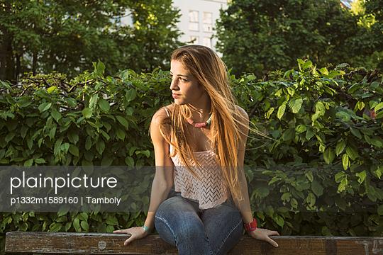 Junge Frau sitzt auf einer Parkbank - p1332m1589160 von Tamboly