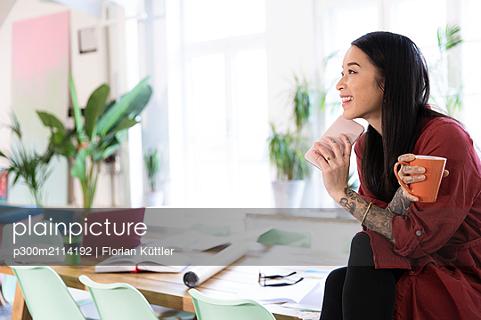 Smiling woman with cellphone sitting on table in modern office - p300m2114192 by Florian Küttler