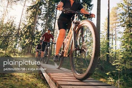 Female friends mountain biking on boardwalk by trees in forest - p426m2036738 by Katja Kircher