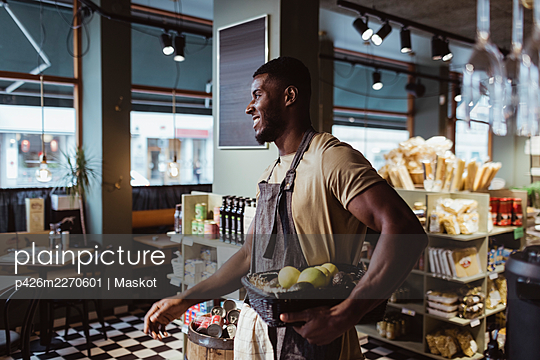 Young male owner standing with fruit basket in deli store - p426m2270601 by Maskot