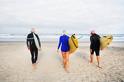 Senior woman and two senior men on a beach, wearing wetsuits and carrying surfboards. - p1100m1177584 by Mint Images