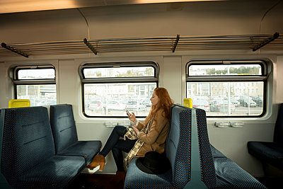 Beautiful woman using mobile phone while travelling in train - p1315m2014350 by Wavebreak