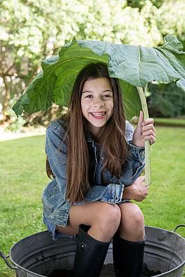 Portrait of smiling girl under big leaf sitting in tub in the garden - p300m2062390 von Petra Stockhausen