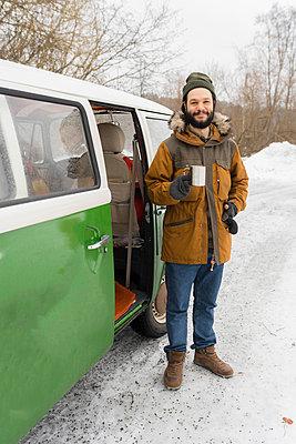 Portrait of smiling man with electric van in winter landscape, Kuopio, Finland - p300m2114847 von Petra Silie