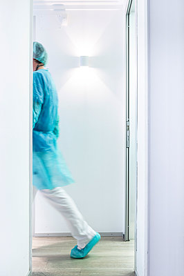Mature male dentist walking in illuminated hallway - p300m2198388 by Jose Luis CARRASCOSA