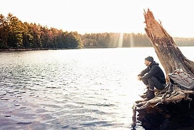 Man sitting on boulder by still lake - p429m1450397 by Hugh Whitaker