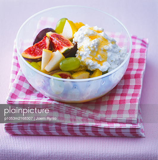 Fruit salad with figs, grapes, pear and cottage cheese - p1053m2168307 by Joern Rynio
