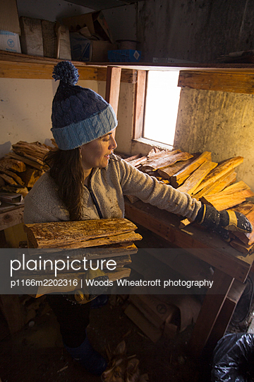 A woman building a fire in a rustic sauna. - p1166m2202316 by Woods Wheatcroft photography