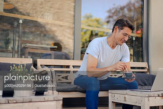 Mature businessman sitting in coffee shop, drinking coffee, using laptop - p300m2029156 von Gustafsson