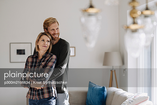 Couple embracing at home - p300m2166634 by Kniel Synnatzschke
