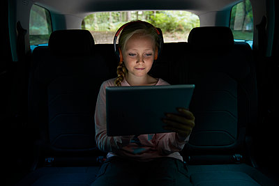 Girl with headphones and digital tablet in back seat of car - p1023m2161810 by Himalayan Pics