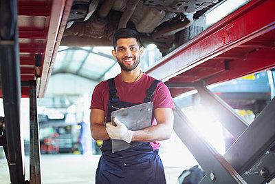 Portrait confident male mechanic with clipboard working under car in auto repair shop - p1023m2196757 by Tom Merton