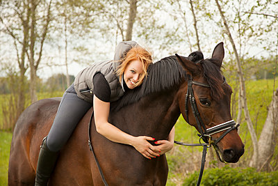 Smiling young woman riding horse - p300m1460584 by Christina Falkenberg