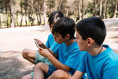 Three boys in blue t-shirts using smartphone - p300m2131986 von Jose Luis CARRASCOSA