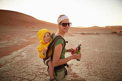 Mother and son on sand dune, Namib Naukluft National Park, Namib Desert, Sossusvlei, Dead Vlei, Africa - p429m1029660 by Stephen Lux