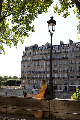 Woman reading on her laptop in the street of Paris - p445m2185208 by Marie Docher