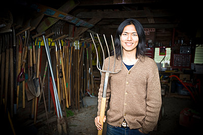Japanese gardener holding pitchfork in barn - p555m1305870 by Jed Share/Kaoru Share
