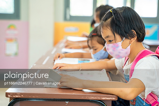 Group of asian children wearing protective mask to Protect Again - p1166m2246777 by Cavan Images