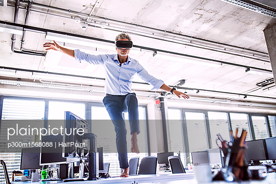 Barefoot mature businessman on desk in office wearing VR glasses - p300m1568088 by HalfPoint
