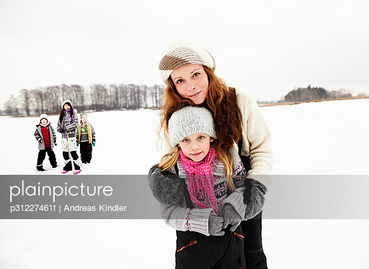 Portrait of mother embracing daughter in snow, friends in background - p31227461f by Andreas Kindler