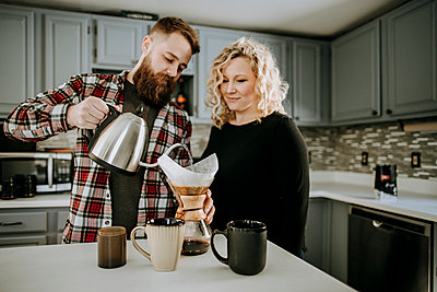 man pours hot water into coffee pour over while wife looks on - p1166m2171767 by Cavan Images