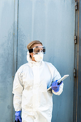 Female scientist wearing protective suit and mask with tablet in front of a door - p300m2170969 by Eloisa Ramos